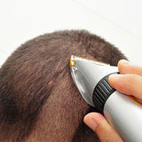 Man cutting his hair with an electric hair clipper. A man man cutting his hair with an electric hair clipper Royalty Free Stock Image