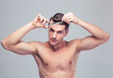 Man cutting his hair Stock Images