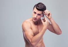 Man cutting his hair Stock Photo
