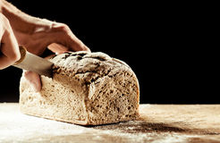 Man cutting a homemade loaf of wholegrain bread Royalty Free Stock Photos