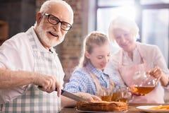 Man cutting homemade pie. While women pouring tea stock photo