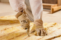 Man cutting insulation material for building