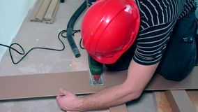 Man cutting laminate flooring with electric hand saw. stock video footage