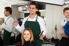 Man cutting long hair of girl in hairdressing saloon Royalty Free Stock Photos