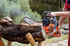 Man cutting lumber with chainsaw Stock Images
