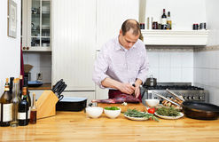 Man Cutting Meat On Chopping Board Stock Images