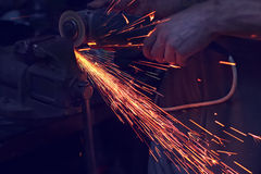 Man cutting metal with angle grinder. Sparks while grinding iron Stock Images