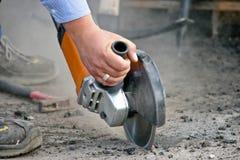 Man cutting a metal bar with a circular saw Stock Photos