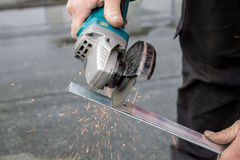 Man cutting a metal bar with a circular saw Royalty Free Stock Images