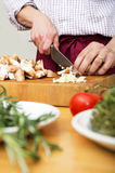 Man Cutting Mushrooms On Chopping Board stock photography