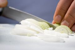 Man cutting an onion. A detail image of a man cutting an white young onion Stock Photography