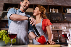 Man cutting paprika and talking to wife Royalty Free Stock Photo