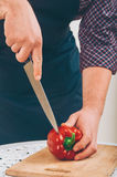 Man cutting pepper. Salad preparation - cutting red pepper into pieces Royalty Free Stock Image