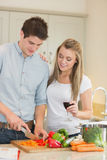 Man cutting peppers with woman drinking wine Royalty Free Stock Image