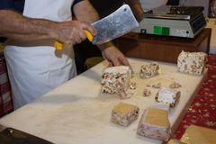 Man cutting a piece of torrone sweet at Golosaria 2013 in Milan, Italy Stock Images