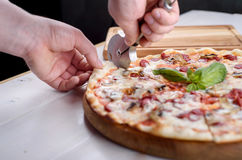 The man is cutting pizza with mushrooms. And sausages Stock Photo