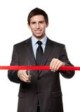 A man cutting a red ribbon with scissors Royalty Free Stock Photo