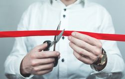 Man cutting red ribbon with scissors. Royalty Free Stock Photos