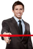 A man cutting a red satin ribbon Royalty Free Stock Image