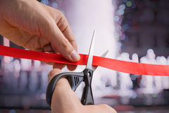 Man is cutting red tape or ribbon against defocused background. Opening ceremonial Royalty Free Stock Images