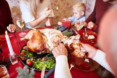 Man cutting roasted turkey on a table background. Family enjoying autumn holidays. Thanksgiving dinner concept. Close-up of a man slicing a hot, roasted turkey stock photos
