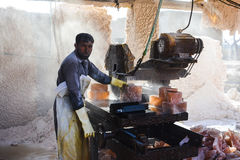 A man cutting rock salt to make tiles. Somewhere near Quaidabad, Khushab, Pakistan Stock Image