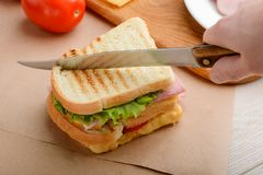 Man cutting a sandwich. With a knife in two triangle slices. Grilled meal with lettuce, tomato, ham and cheese stock images