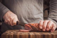 Man cutting sausage Stock Photo
