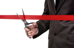 A man cutting a scarlet satin ribbon Royalty Free Stock Images