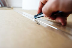 Man cutting with sharp cutter knife a cardboard box to open it stock image