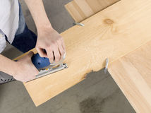 Man cutting sheet of a wooden plank Royalty Free Stock Images