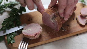 Man is cutting slice of smoked ham stock video footage