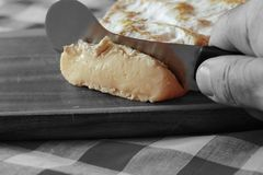 Man cutting a slice of Somerset Brie with a cheese knife Royalty Free Stock Photography