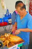 A man cutting soy sauce poached Squid at a stall Royalty Free Stock Photos