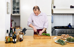 Man Cutting Spring Onions In Kitchen Stock Photography