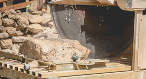 Man cutting a stone with a water saw Stock Images