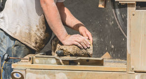 Man cutting a stone with a water saw Stock Image