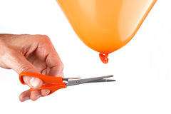 Man cutting the string of a balloon with scissors Stock Photography