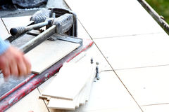 Man cutting tile by cutter Royalty Free Stock Images