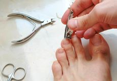 Man cutting toenails with clipper. Male cut toenails on foot. Foot and toes close-up. Top view. Man cutting toenails with clipper. Male cut toenails on foot Royalty Free Stock Images
