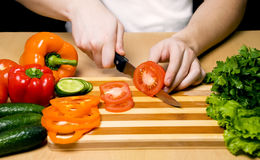 Man cutting vegetables. Hands cutting vegetables on a wood board Stock Images