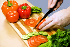 Man cutting vegetables. Hands cutting vegetables on a wood board Stock Photo