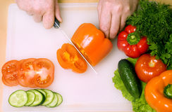 Man cutting vegetables. Hands cutting vegetables on a white board Royalty Free Stock Photos