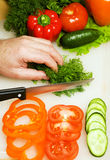 Man cutting vegetables. Hands cutting vegetables on a white board Stock Photo