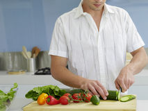 Man Cutting Vegetables In Domestic Kitchen Royalty Free Stock Photos