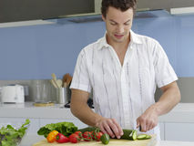 Man Cutting Vegetables In Domestic Kitchen Stock Image