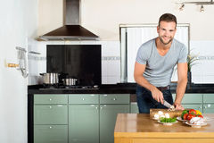 Man Cutting Vegetables At Kitchen Counter stock photos