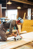 Man Cutting Wood in Carpentry Workshop. Portrait of man wearing workers uniform and earmuffs cutting large wooden board in woodworking shop of furniture factory Stock Photography