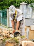 Man cutting wood with a chainsaw. Man cutting big wood with a chainsaw Royalty Free Stock Images