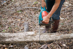 Man cutting the wood with chainsaw. Man cutting the log of wood with chainsaw Stock Photo